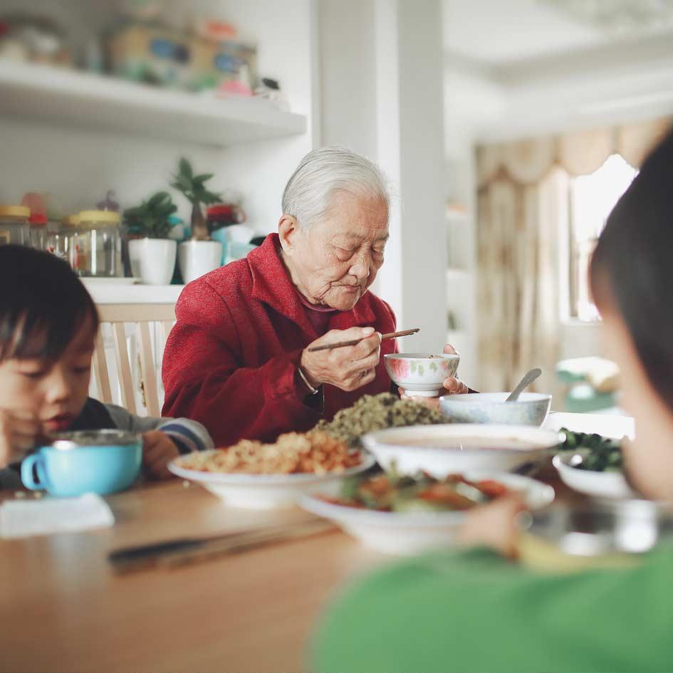 An elderly man eating dinner with his grandchildren