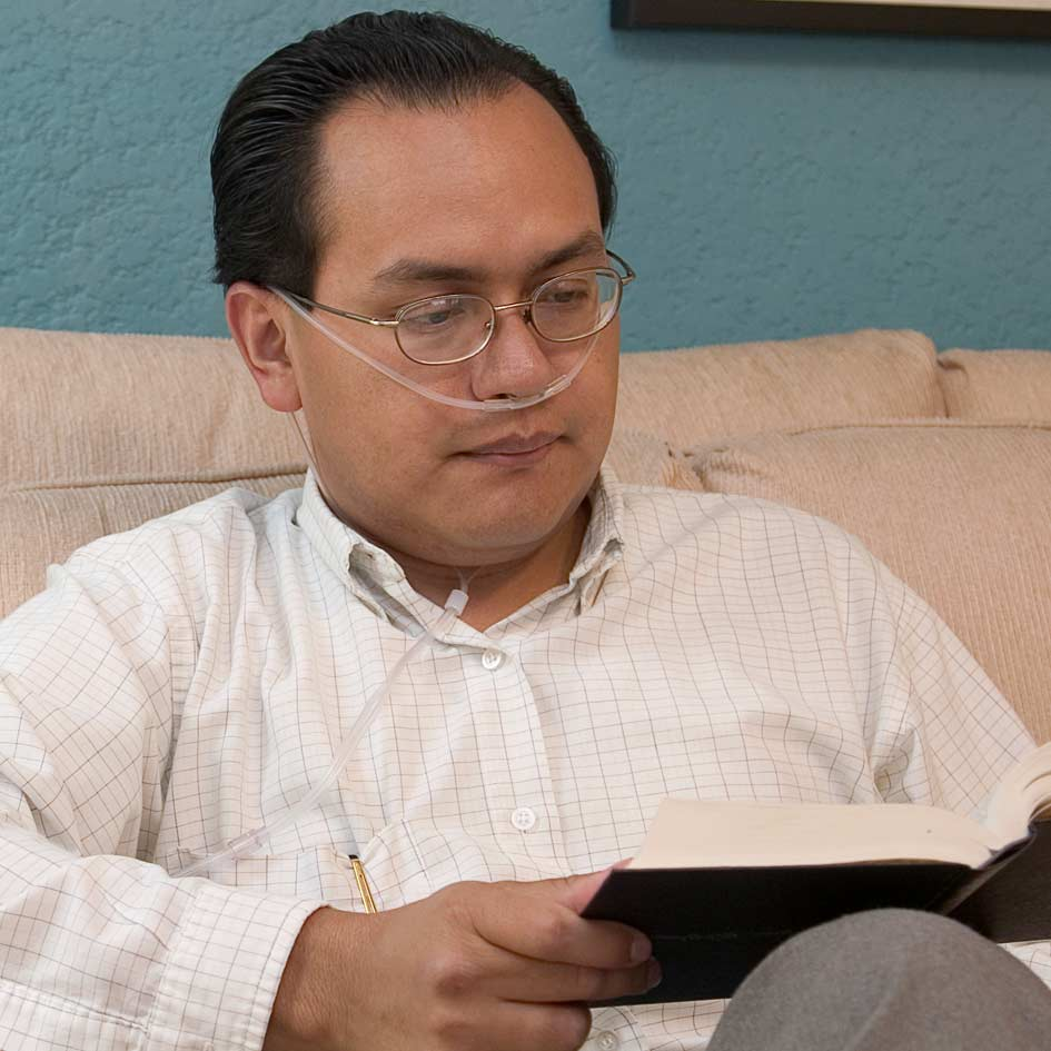 A man receiving oxygen whilst reading a book at home
