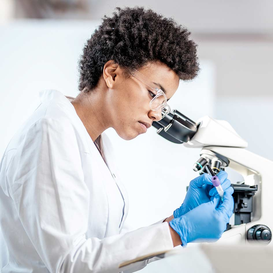 A woman in a laboratory next to a microscope