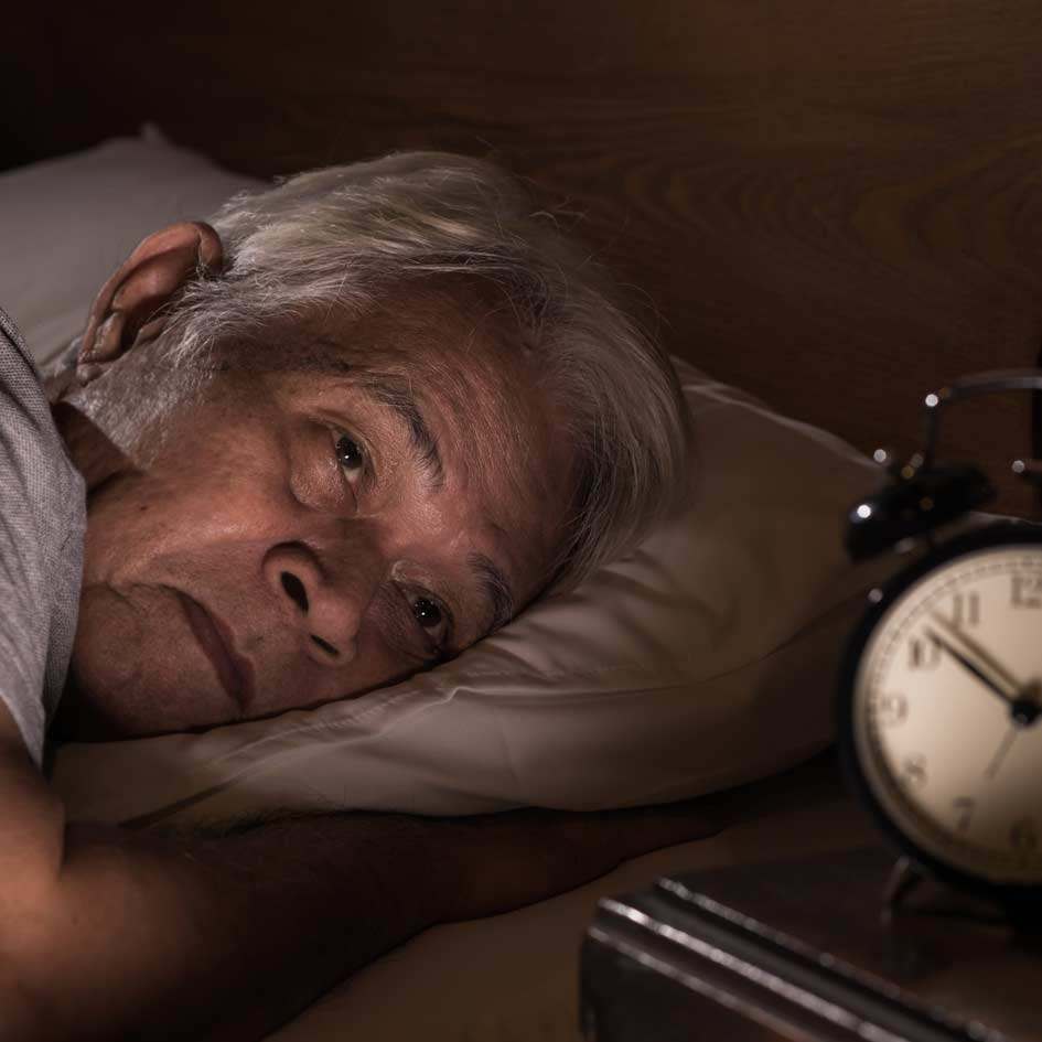 A man in bed looking at the clock