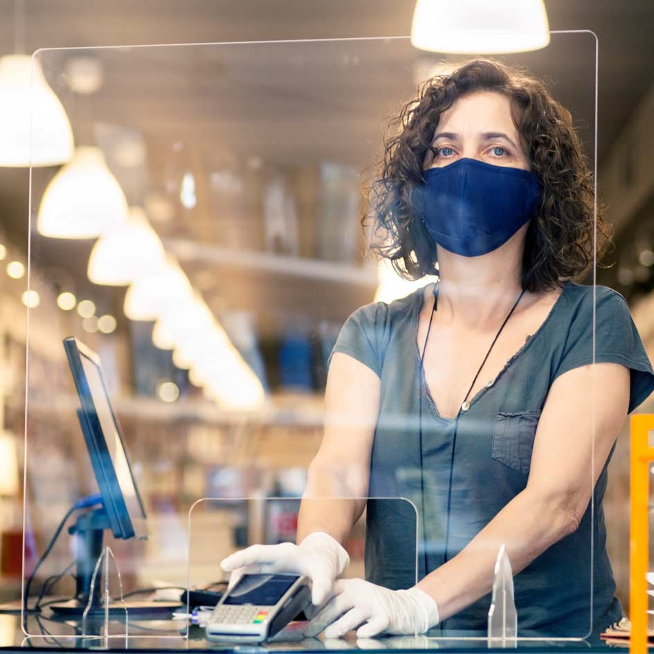 A shop worker wearing a face mask behind a protective screen