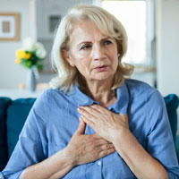 A woman gently clutching her chest
