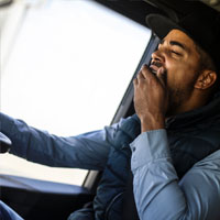 A man yawning whilst driving